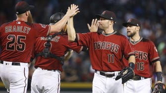The Diamondbacks' Archie Bradley (25) high-fives A.J. Pollock (11) after a 4-2 win over the Padres at Chase Field in Phoenix, Ariz. on April 22, 2018.