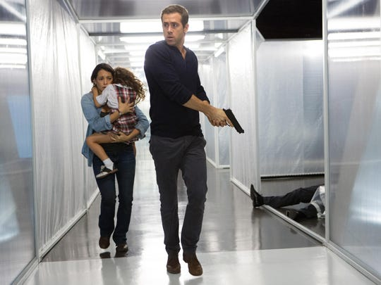 """Natalie Martinez, from left, as Madeline, and daughter, Jaynee-Lynne Kinchen as Anna, fleeing with Ryan Reynolds as Young Damian in the psychological science-fiction thriller """"Self/less."""" (Alan Markfield/Gramercy Pictures via AP)"""