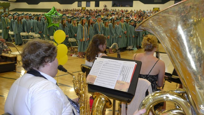 "Ashwaubenon High School junior Tyler Moore, bottom left, plays baritone saxophone as the school band plays ""Pomp and Circumstance"" at the start of Ashwaubenon's commencement for the Class of 2016 on Sunday, June 5, 2016."