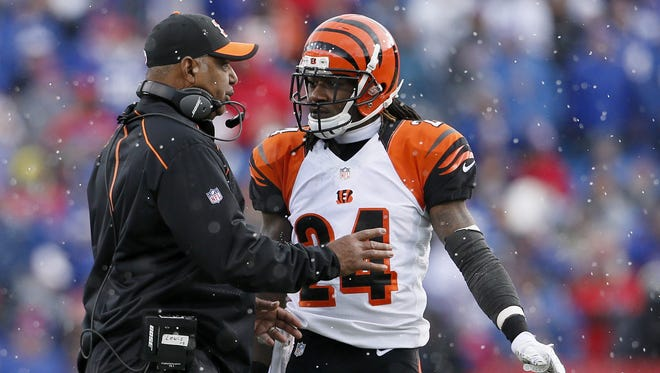 Bengals head coach Marvin Lewis talks with cornerback Adam Jones as the now falls again.