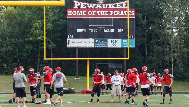Players run through drills during pre-season football practice at Pewaukee High School on Thursday, August 3, 2017.