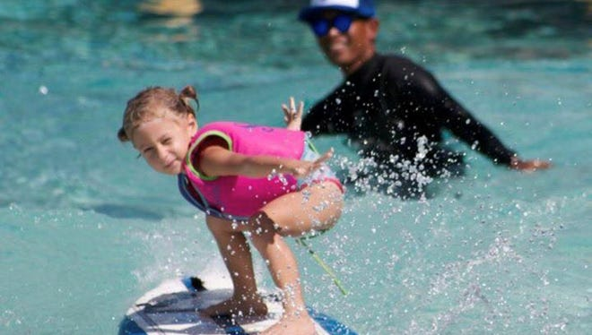 A girl shows off her surfing form at the Guam Hui Nalu Ocean Club at the Billabong Manahak Jr. Surf Competition at the Onward Beach Resort Nov. 11.