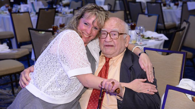 Joyce Fowlkes gets a congratulatory hug from legendary TV actor Ed Asner, master of ceremonies for the 2015 Hero Awards presentation of the Assisted Living Federation of America.