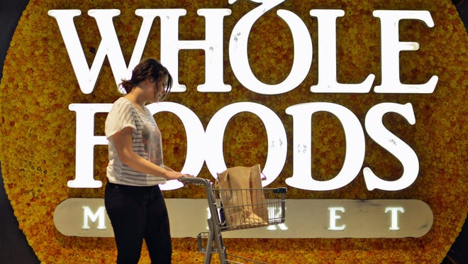 A woman pushing a shopping cart in front of a Whole Foods Market sign.
