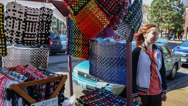 Elsa Heising stands along side her first ever booth she has had at the Eugene Saturday Market, where she sells rugs and potholders made from recycled T-shirts on Saturday, April 7, 2018.