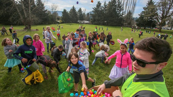 Caleb Plummer (right) tosses a few of the 25,000 eggs filled with toys and other treats that were distributed for a past Willamalane Park and Recreation District's MEGGA egg hunt at Lively Park in Springfield.