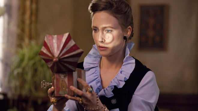 """Vera Farmiga peers into a child's toy that may hold an evil secret in the Wilmington-shot horror film """"The Conjuring,"""" which was released in theaters in 2013."""