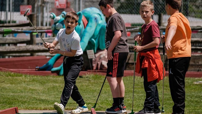 Connor Holt, 8, of Fairlawn reacts to a putt during his second round of miniature golf on Sunday with friends at Rinky Dink Family Fun Center in Medina Township.