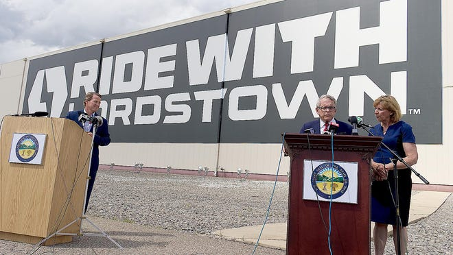During a news conference outside the Lordstown Motors plant, Lt. Gov. Jon Husted, left, Gov. Mike DeWine and his wife, Fran DeWine, discuss the new electric vehicle plant Wednesday.