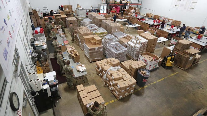 Members of 145th National Guard unit of Stow help volunteers at the Akron-Canton Regional Foodbank fill boxes with non-perishable food items that will be delivered to area food pantries Monday, March 23, 2020, in Akron, Ohio.