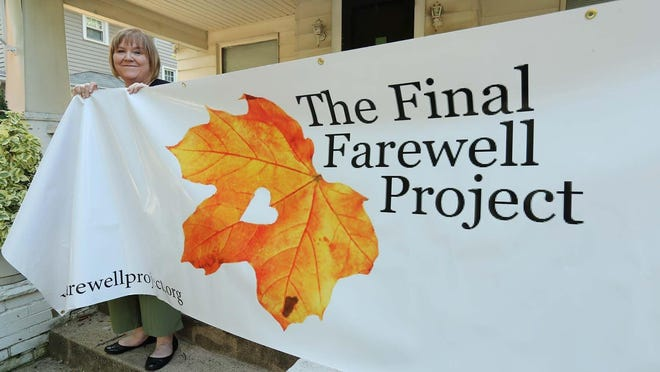 Dorene Sherman, founder of The Final Farewell Project that helps indigent families bury loved ones with dignity and respect, stands with the group's banner at her home Thursday, Aug. 13, 2020 in Akron, Ohio.