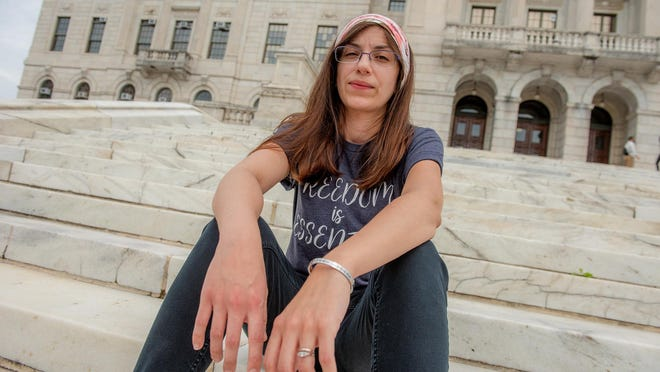 Sara Alvizures, a Central Falls mother of four, had a miscarriage in April. She wanted nothing more than to be comforted by her church family. But Governor Raimondo's executive orders had churches shuttered. Here, Alvizures is at the State House.