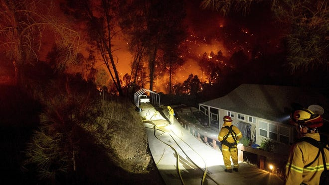 Firefighters protect a home in the Berryessa Estates neighborhood of unincorporated Napa County, Calif., in August as the LNU Lightning Complex fires burn on. The blaze forced thousands to flee and destroyed hundreds of homes.