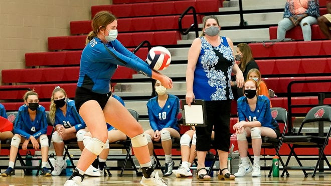 McCallum's Preslie Boswell passes the ball over the net against Weiss as head coach Amy Brodbeck looks on. McCallum beat the Wolves in straight sets Sept. 22 at Weiss High School.