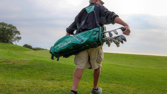 "Dave Bart, Metacomet Golf Club's last full-time caddie, heads out on a ""loop."""