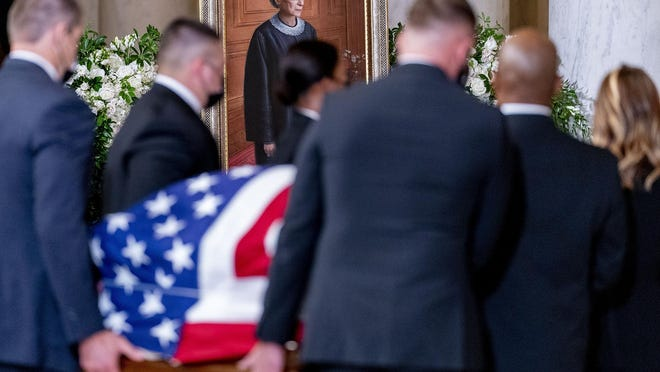 The flag-draped casket of Justice Ruth Bader Ginsburg, carried by Supreme Court police officers, arrives in the Great Hall at the Supreme Court in Washington on Wednesday. In the background is a portrait of the late justice, who died of pancreatic cancer on Sept. 18.