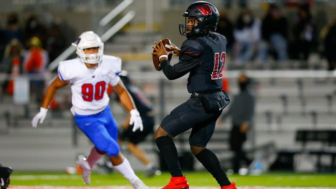 Weiss quarterback Dior Bradfield hunts for a receiver during the Wolves' 63-34 win over Leander at The Pfield in Pflugerville. Bradfield threw for 366 yards and five touchdowns on the night.