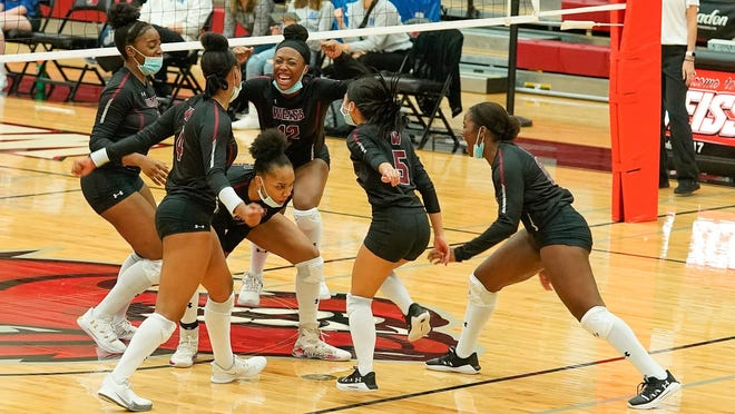 Weiss squad members celebrate winning a point in a September match versus McCallum. The Wolves earned American-Statesman team of the week honors by defeating Connally and Bastrop last week.