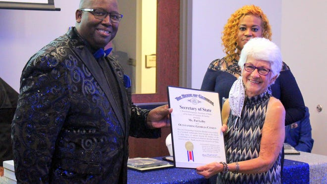 Pat Leiby, right, receives an MLK Drum Major award from Rep. Carl Gilliard, founder of Feed the Hungry.