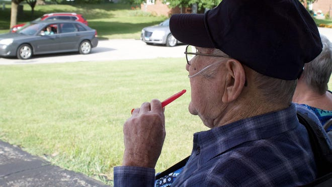 Frank Folden of Monmouth waves to socially distanced visitors on his 88th birthday.
