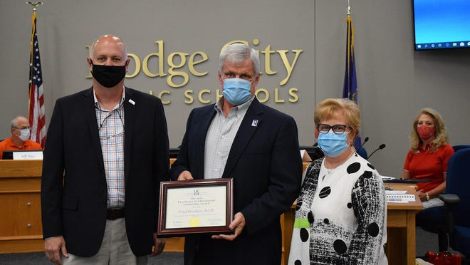 USD 443 Superintendent of Schools Fred Dierksen holds his 2020 UCEA Excellence in Education Leadership Award, presented to him by Donna Augustine-Shaw and Jerry Johnson from K-State's College of Education, at the Aug. 24 USD 443 Board of Education meeting.