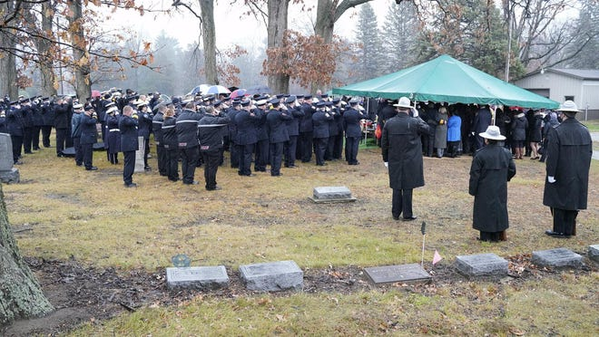 Firefighters and other first responders salute Wednesday at Pleasant View Cemetery during the graveside service for Joe Gallo, a Blissfield Township fire captain and Madison Township firefighter/EMT.