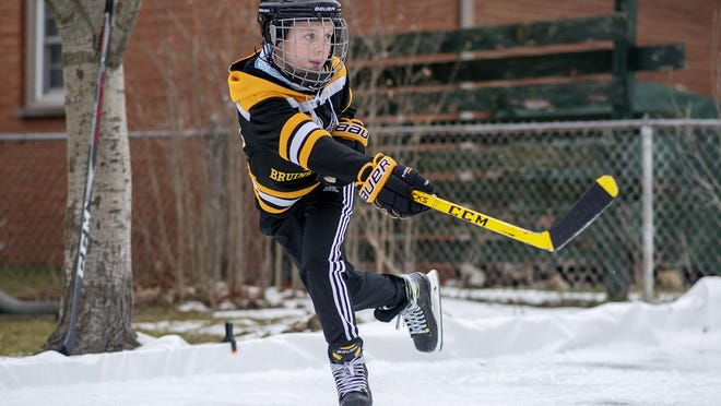 Bronson Jones, 10, practices hockey in his backyard on Monday, Jan. 11, 2021 in Battle Creek, Mich. The backyard ice rink was constructed by his father, Justin Jones.
