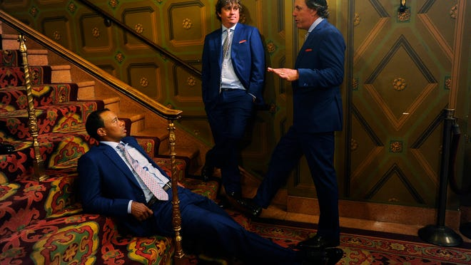 Tiger Woods, Jason Dufner and Phil Mickelson, wearing suits provided by Ted Silver, wait to go onstage during the opening ceremonies at Columbus Commons prior to the start of The Presidents Cup at Muirfield Village Golf Club in October of 2013.