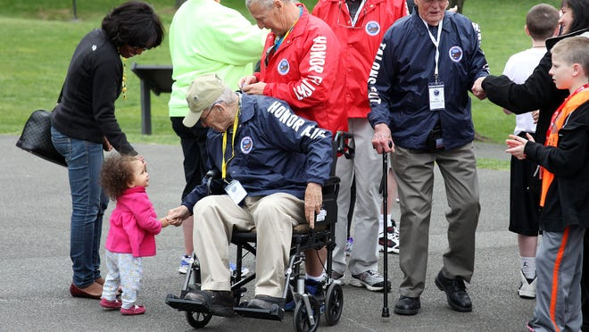 Robert Matheson shakes hands with a little girl who was at the tail-end of a crowd gathered to welcome World War II veterans to Iwo Jima Memorial Saturday afternoon.