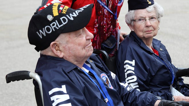 Merle Knight looks over at her husband, Maynard, while talking about their service during World War II.