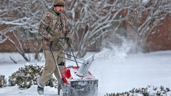 Michael Williams, with the Butler University grounds department, snow blows at the Efroymson Center for Creative Writing, after an overnight snow, Tuesday, January 6, 2015.