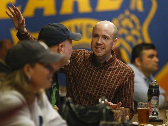 Bill Fasano (facing camera) chats at the bar of the