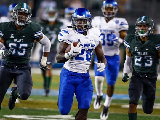 University of Memphis running back Doroland Dorceus (front) scrambles past the Tulane University defense for a 61 yard run during fourth quarter action at Yulman Stadium in New Orleans.
