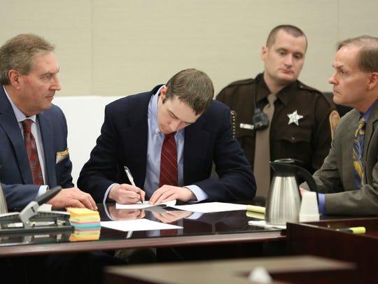 David Eisenhauer, center, signs a no contest plea next
