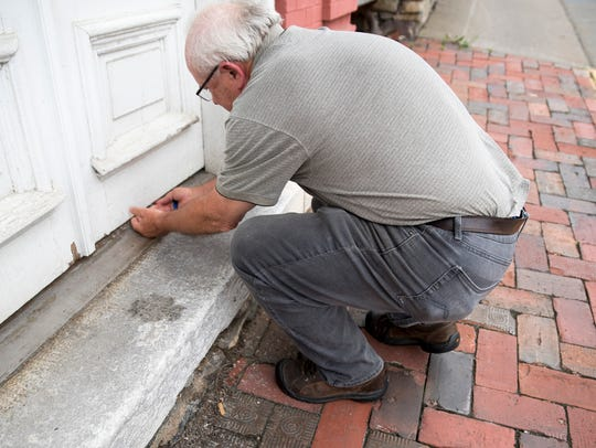 A Fairfax County, Va., man slides a thank-you card underneath the Red Hen's door in Lexington.