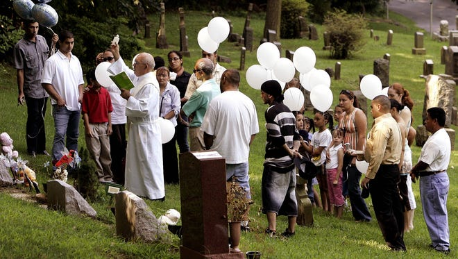 Friends and family gather as Deacon Abraham Santiago of St. Joseph's Church blesses the headstone of Elijah Santana and David Maldonado Jr. at Oakland Cemetery in Yonkers July 29, 2006, on the one-year anniversary of the scalding deaths of the two young boys.