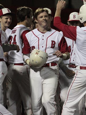 Kyle Rowe of Beechwood is congratulated at home plate after knocking it out of the park for the Tigers against NewCath.