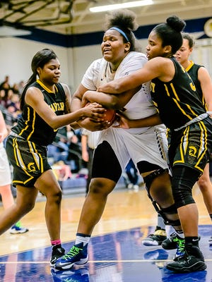 Tazjah Pruitt ,left, and Kyra Patterson, right, of Waverly wrap up the ball after Imania Baker of Haslett secured a rebound.