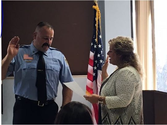 Capt. Michael Carey receives the oath of office Monday at the Mansfield Fire Department by  Service-Safety Director Lori Cope.