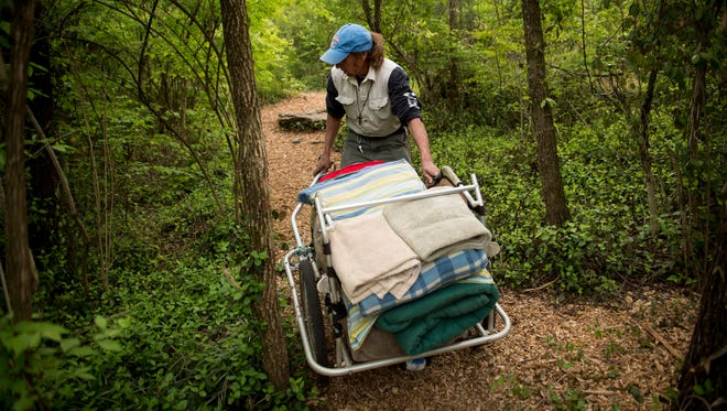 Chris Scott Fieselman, who is known as Captain, carries a load of clean laundry to his tent at a homeless camp on the grounds of Fort Negley, Wednesday, April 13, 2016, in Nashville, Tenn. The camp is facing an 11 p.m. deadline on Friday to vacate the land.