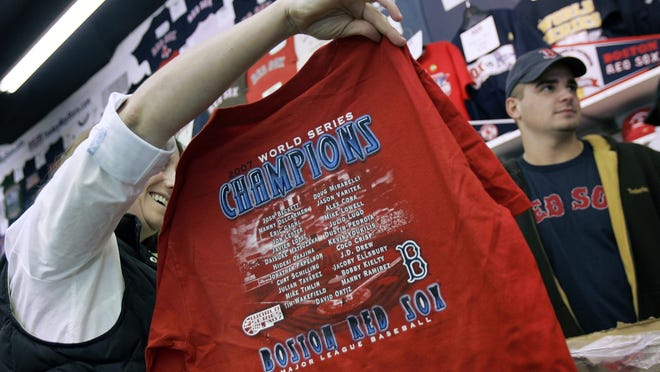In this photo from October 2007, a woman holds up a Red Sox World Series shirt at a souvenir shop near Fenway Park. Ballpark area businesses are struggling during the 2020 season while fans are not in attendance due to the pandemic.