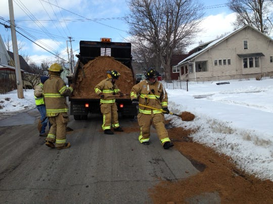 Firefighters spread dirt over fuel left from a spill at Emmett Street and McKinley Avenue on Monday afternoon.