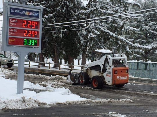 Snow removal is underway Thursday morning at M&J convenience store on Swannanoa River Road.