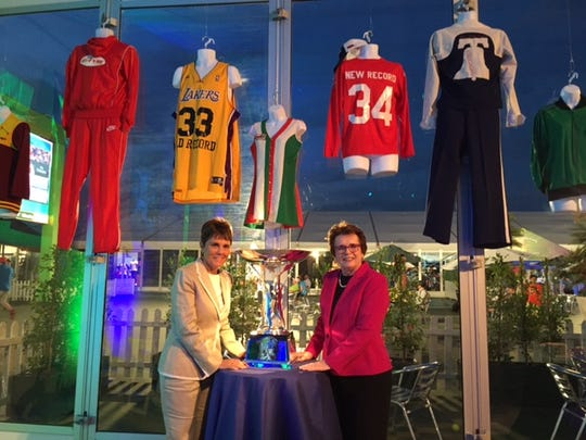Ilana Kloss and Billie Jean King with the King Trophy (old World Team Tennis uniforms are seen in the background) during Mylan WTT (World Team Tennis) 40th anniversary celebration at BNP Paribas Open in Indian Wells on Monday, March 16, 2015.