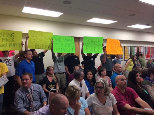 Supporters of Tim Rutt hold up signs at a Gilbert Public