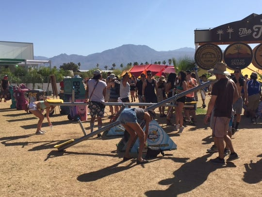 Coachella attendees plug their phones into teeter-totters, which will charge them as they ride.