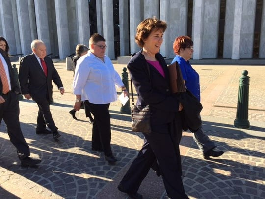 Jayne Rowse, left, led by attorney Carole Stanyar  makes her way to the U.S. Supreme Court with partner April DeBoer Tuesday, April 28, 2015, in Washington, D.C., with the hope of their case overturning the ban on same-sex marriage nationally.
