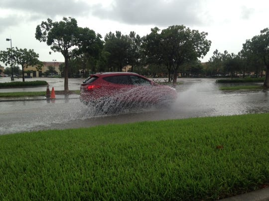 Cars plow through flooded roadways at Coconut Point mall