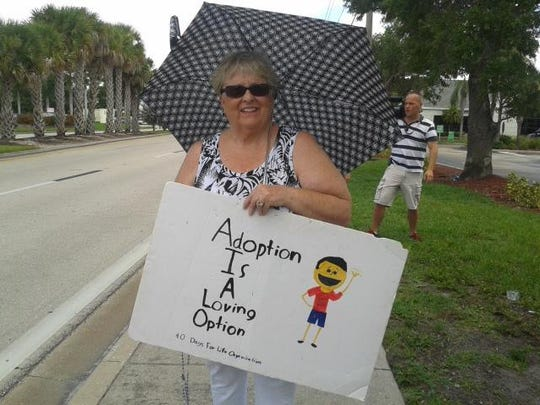 Pro-life protester, Mary Kay, holds sign by roadside.
