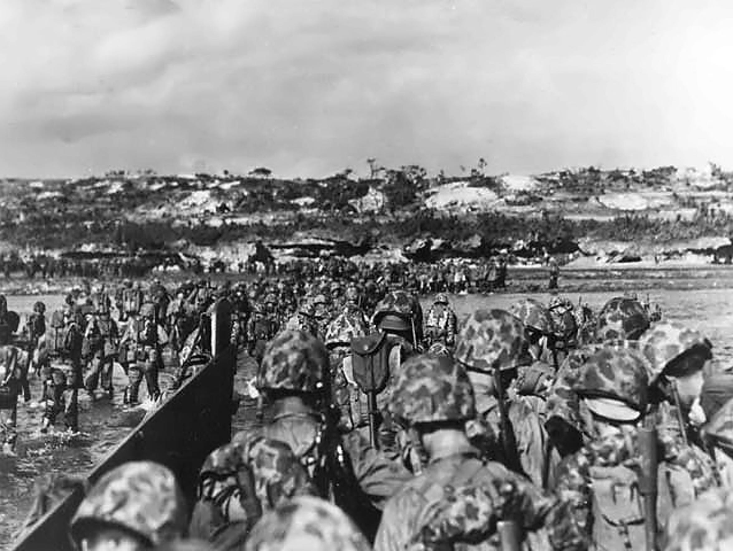 U.S. Marine reinforcements wade ashore to support the